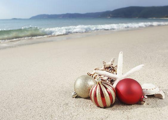 christmas balls and seashells on the beach near the sea